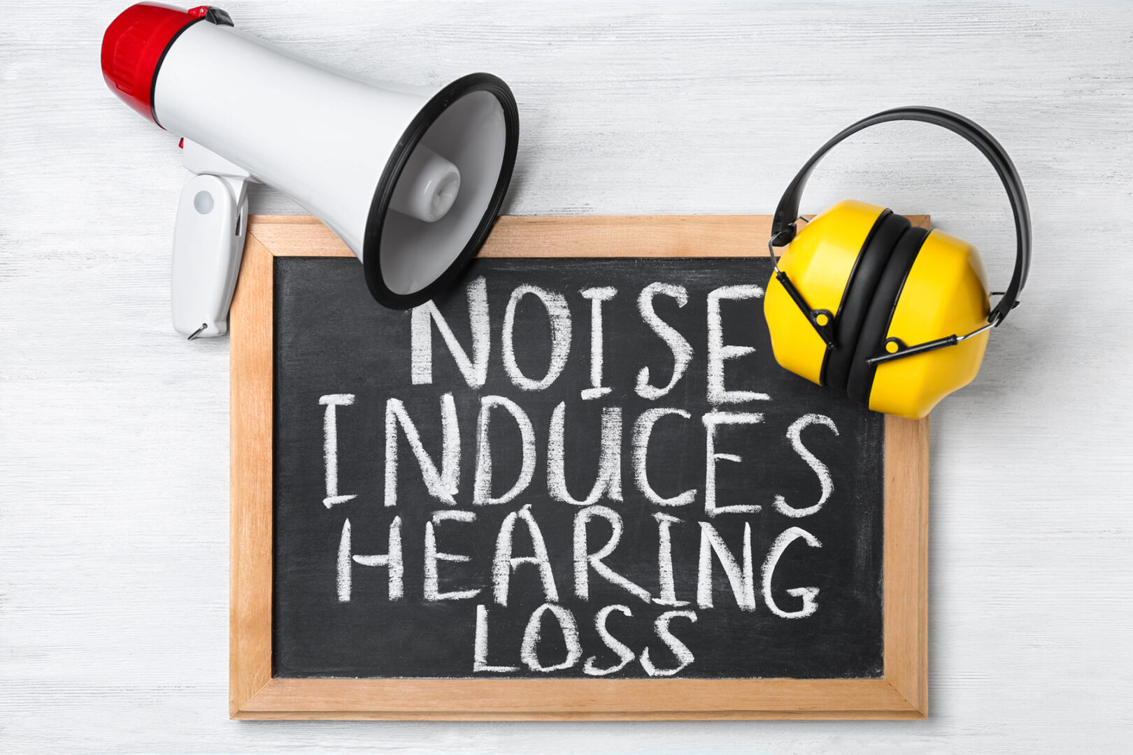 Headphones, megaphone and chalkboard with text NOISE INDUCES HEARING LOSS on table